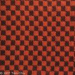Handwoven sample with black warp, orange weft, 1/3 vs. 3/1 twill blocks