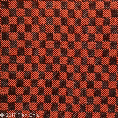 Handwoven sample with black warp, orange weft, 1/3 vs. 3/1 twill blocks