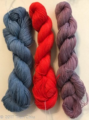 three yarns, one orange, one dull blue, one dull purple
