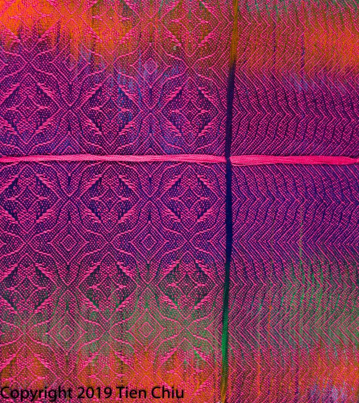 A handwoven sample showing a painted warp in purple, orange, and green painted warp with hot pink weft