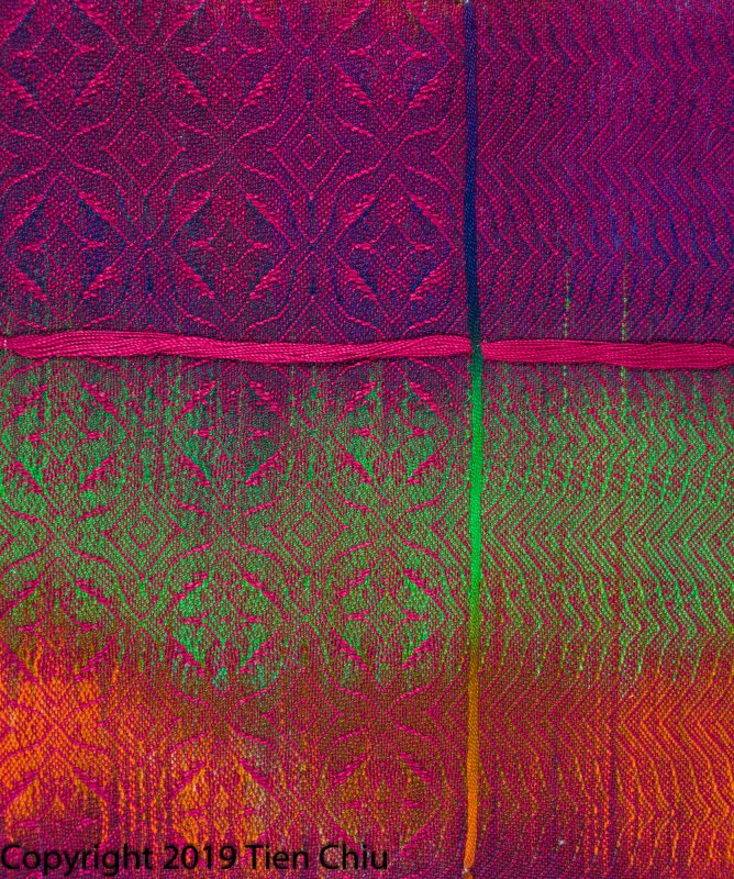 A handwoven sample showing a painted warp in purple, orange, and green painted warp with cranberry weft