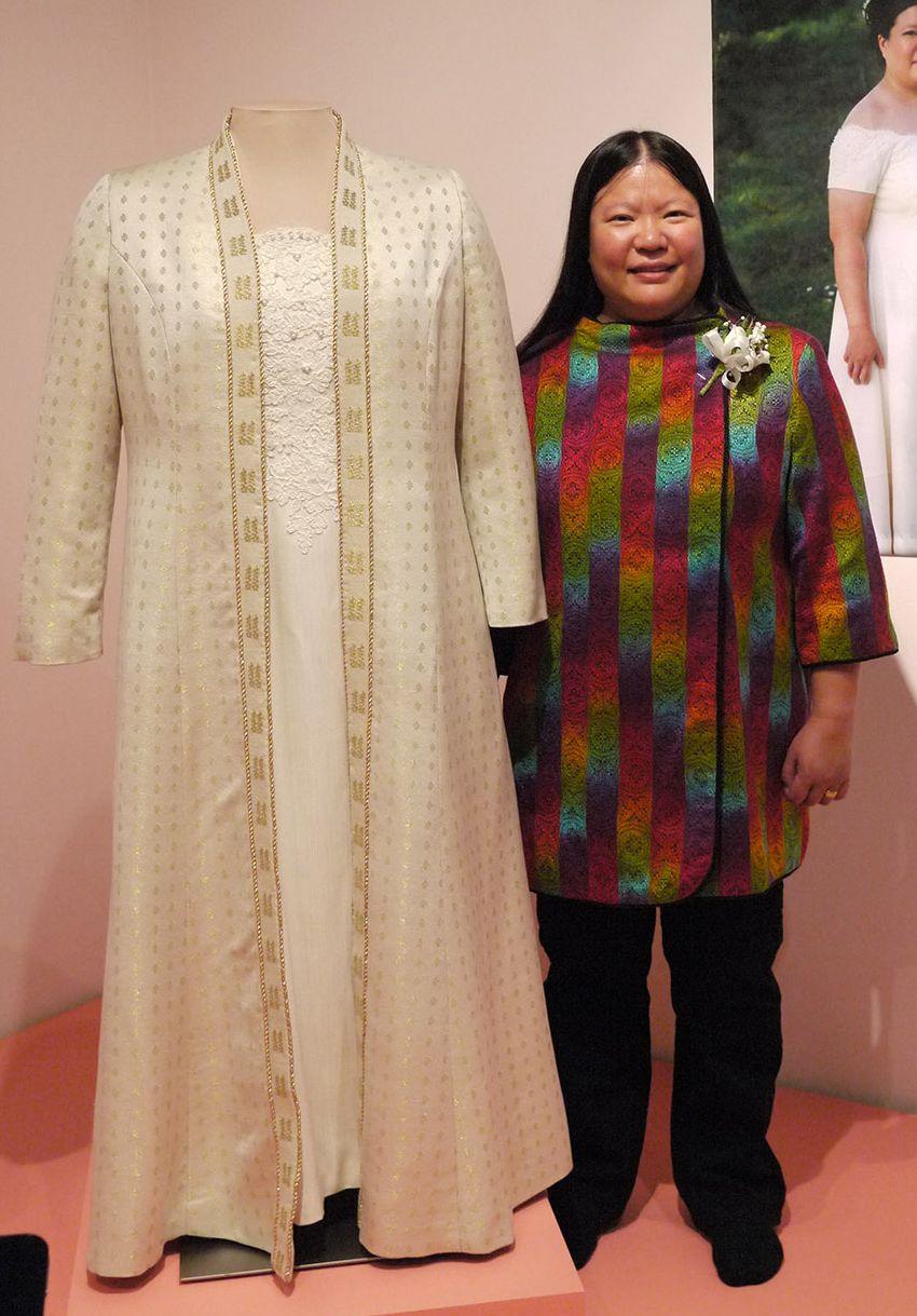 Tien with wedding dress at museum exhibit