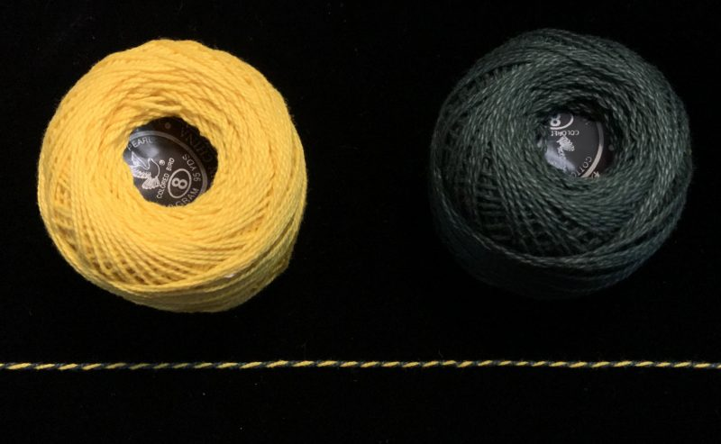 Two balls of yarn, yellow and dark green, which twist together into a barberpole yarn.