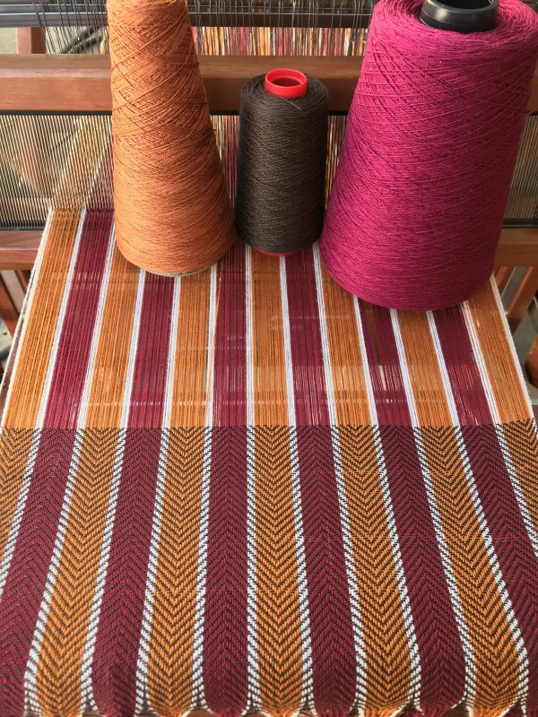 gold, burgundy, and brown yarns on fabric