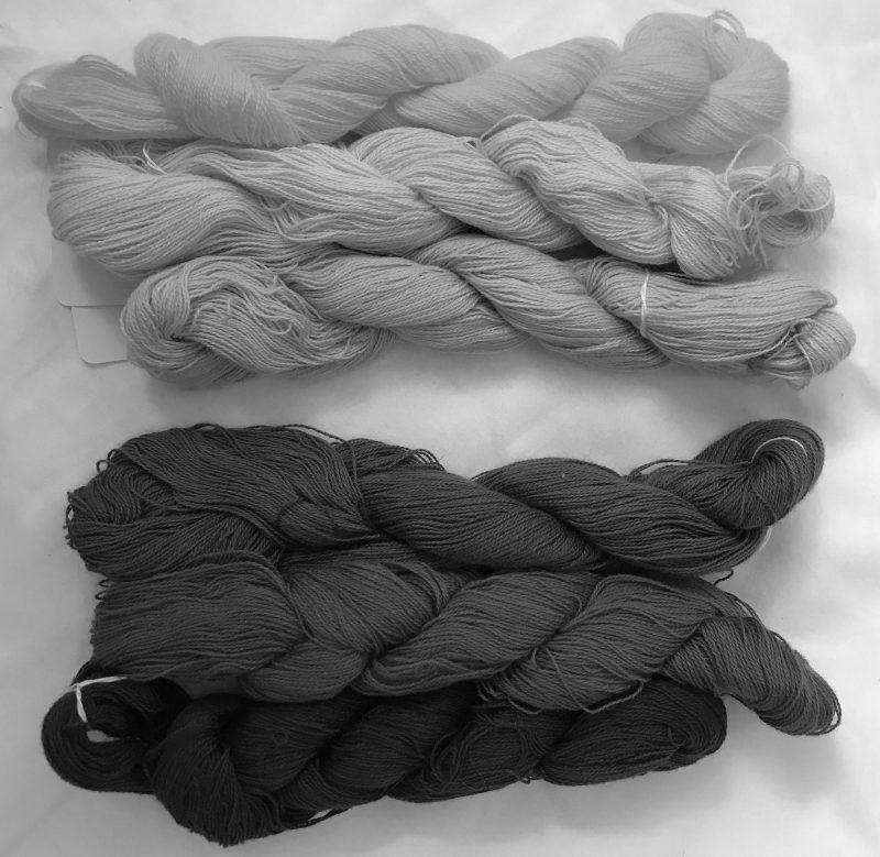 The same skeins in black and white. The top three skeins are nearly the same shade of light gray. THe bottom three skeins are dark to very dark gray.