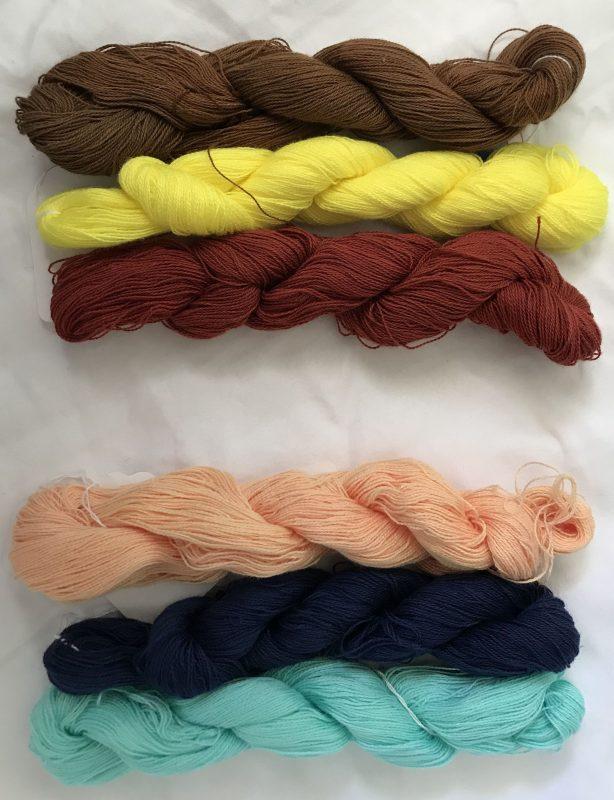 Three warp yarns on top: dark golden brown, light yellow, and dark reddish brown.   Three weft yarns on bottom: pale peach, deep navy, light aqua.